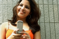 Woman holding mobile phone, smiling, looking away - Asia Images Group