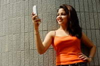 Woman looking at mobile phone, hand on hip - Asia Images Group