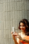 Woman looking at mobile phone, smiling - Asia Images Group
