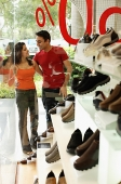 Couple standing outside shoe shop window display - Asia Images Group