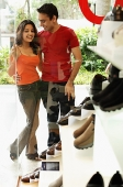 Young man and woman standing outside shoe shop - Asia Images Group