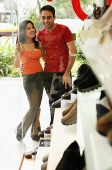 Young man and woman standing side by side outside shoe shop - Asia Images Group