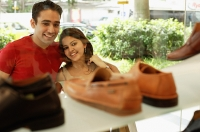 Young man and woman standing outside shoe shop looking at window display - Asia Images Group