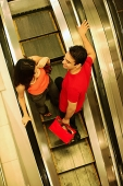 Young man and woman standing on escalator, high angle view - Asia Images Group