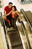 Young man and woman standing on escalator, looking up at camera - Asia Images Group
