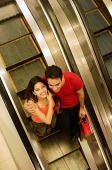 Young man and woman standing on escalator, woman looking up at camera - Asia Images Group