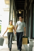 Young man and woman walking, holding hands and carrying shopping bags - Asia Images Group