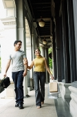 Couple walking, holding hands and carrying shopping bags - Asia Images Group