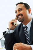 Businessman using telephone, smiling - Asia Images Group