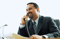 Businessman using telephone in office, smiling - Asia Images Group