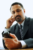 Businessman looking at PDA phone - Asia Images Group