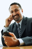 Businessman looking at PDA phone, smiling - Asia Images Group