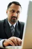 Businessman at desk, using laptop - Asia Images Group