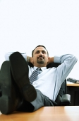 Businessman in office, hands behind head, feet on desk - Asia Images Group