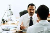 Two businessmen in office having a discussion - Asia Images Group