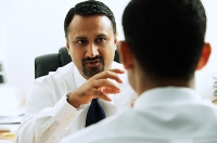 Two businessmen in office having a discussion, face to face - Asia Images Group