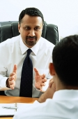 Two businessmen in office talking - Asia Images Group