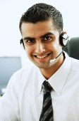Man using headset, smiling at camera - Asia Images Group