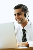Executive using headset, smiling, using laptop - Asia Images Group