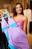 Young woman holding dress on hanger, smiling - Asia Images Group