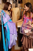 Two women in dress shop, looking at clothes - Asia Images Group