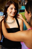 Women adjusting necklace for her friend - Asia Images Group