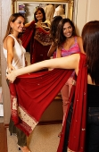 Women in shop trying on saris - Asia Images Group