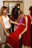 Women in shop looking at and trying on saris - Asia Images Group