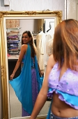 Woman wearing sari, looking at herself in mirror - Asia Images Group