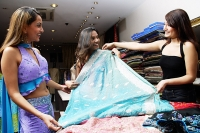 Women in shop looking at cloth for saris - Asia Images Group