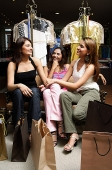 Three women sitting in clothing store, talking, shopping bags around them - Asia Images Group