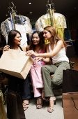 Three women sitting in clothing store, looking inside shopping bag - Asia Images Group