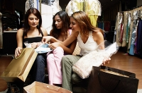 Three women sitting in clothing store with items purchased - Asia Images Group