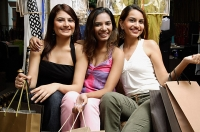 Three women sitting and holding shopping bags - Asia Images Group