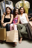 Three women sitting and holding shopping bags, looking at camera - Asia Images Group