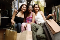 Three women with shopping bags, looking at camera - Asia Images Group