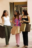 Three women carrying shopping bags - Asia Images Group