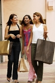 Three women carrying shopping bags, walking side by side - Asia Images Group