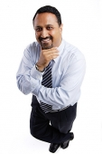 Businessman looking up at camera, arms crossed, hand on chin - Asia Images Group