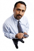 Businessman using PDA, looking at camera - Asia Images Group