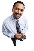 Businessman using PDA, smiling at camera - Asia Images Group