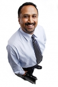 Businessman standing, smiling at camera - Asia Images Group