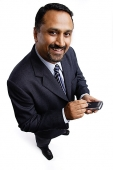 Businessman holding PDA, smiling - Asia Images Group