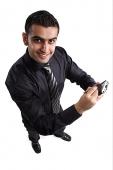 Executive using PDA, looking up at camera - Asia Images Group