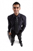 Executive carrying briefcase, hand in pocket - Asia Images Group