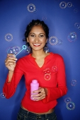 Woman holding bubble wand, bubbles around her - Asia Images Group