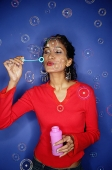 Woman blowing bubbles from bubble wand - Asia Images Group