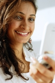 Woman using mobile phone, smiling - Asia Images Group