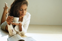 Woman looking at magazine, holding cup and saucer - Asia Images Group