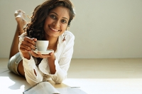 Woman lying on front, holding cup and saucer, smiling - Asia Images Group